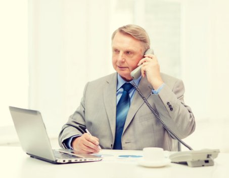 busy older businessman with laptop and telephone
